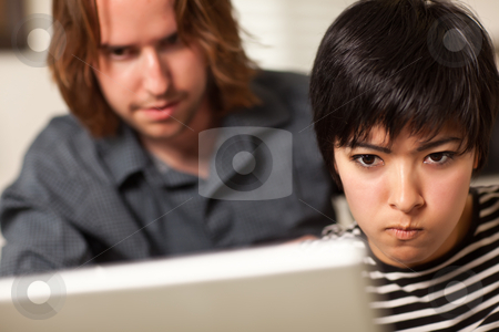 Young Man and Diligent Woman Using Laptop Together stock photo, Young Man and Diligent Woman Using Laptop Computer Together. by Andy Dean