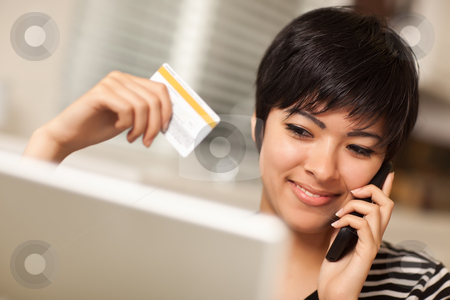 Multiethnic Woman Holding Phone and Credit Card Using Laptop stock photo, Pretty Young Multiethnic Woman Holding Phone and Credit Card Using Laptop. by Andy Dean