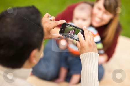 Happy Mixed Race Parents and Baby Boy Taking Self Portraits stock photo, Happy Mixed Race Parents and Baby Boy Taking Self Portraits at the Park. by Andy Dean
