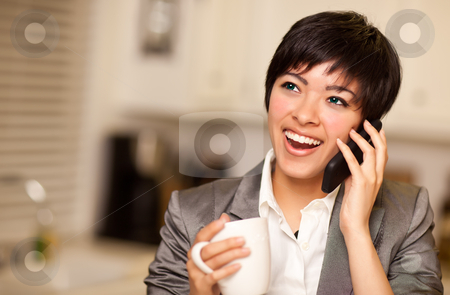 Multiethnic Woman with Coffee Talks on Cell Phone stock photo, Pretty Smiling Multiethnic Woman with Coffee and Talking on a Cell Phone in Her Kitchen. by Andy Dean