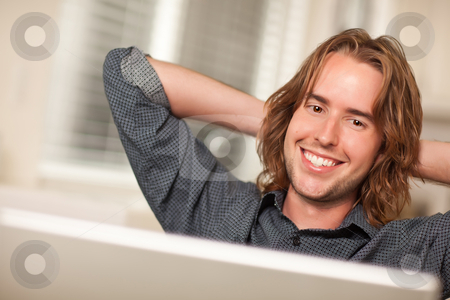 Happy Young Man Using Laptop Computer stock photo, Happy Young Man Using A Laptop Computer with Hands Behind His Head. by Andy Dean