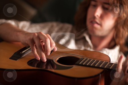 Young Musician Plays His Acoustic Guitar stock photo, Young Musician Plays His Acoustic Guitar under Dramatic Lighting. by Andy Dean