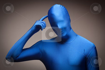 Man Wearing Full Blue Nylon Bodysuite Scratching Head stock photo, Man Wearing Full Blue Nylon Bodysuit Scratching His Head on a Grey Background. by Andy Dean