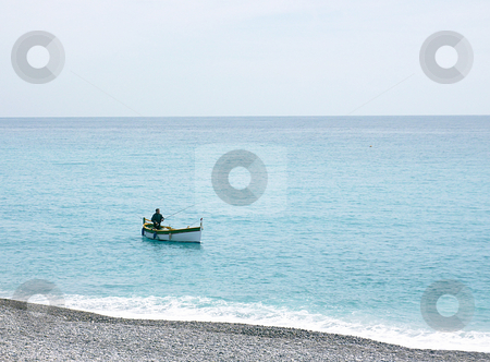 Fishing man at Nice, France stock photo, Fishing man alone  in a small white boat on the clear mediterranean sea by beautiful weather at Nice, France by Elenarts