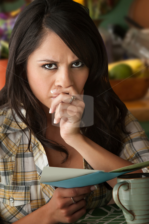 Beautiful Sad Latina Woman with Sympathy Card stock photo, Beautiful Serious Latina Woman at Table in Kitchen Sympathy Card by Scott Griessel
