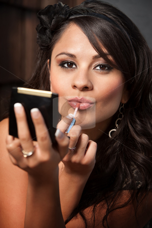 Beautiful Latina Woman with Compact Applying Lip Gloss stock photo, Beautiful Latina Woman Looking into Compact Mirror and Applying Lip Gloss by Scott Griessel