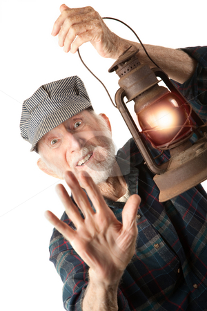 Railroad man holding lantern stock photo, Apprehensive railroad man holding a glowing red lantern. by Scott Griessel