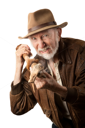 Adventurer or archaeologist defending himself stock photo, Adventurer or archaeologist in brown leather jacket defending himself with abcient weapon by Scott Griessel