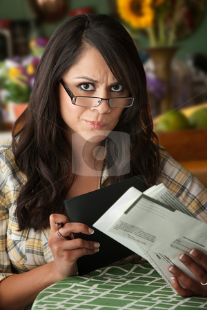 Beautiful Latina Woman with Many Bills stock photo, Beautiful  Latina Woman at Table in Kitchen with Many Bills by Scott Griessel