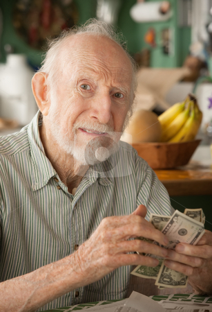 Senior man at home counting money stock photo, Senior man at home with a few dollars counting his money by Scott Griessel