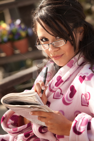 Pretty Hispanic Woman in Bathrobe with Newspaper stock photo, Pretty Hispanic Woman in Bathrobe Doing Newspaper Puzzle by Scott Griessel
