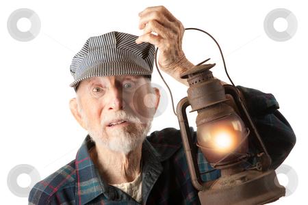 Railroad man holding lantern stock photo, Apprehensive railroad man holding a glowing red lantern. by Scott Griessel