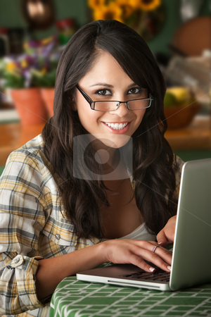 Beautiful Latina Woman with Computer stock photo, Beautiful Latina Woman at table in Kitchen with Computer by Scott Griessel