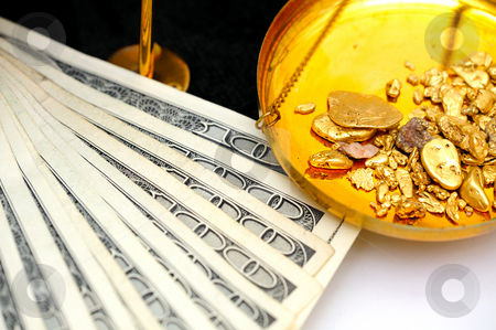 Raw Gold And Money stock photo, Gold nuggets in the pan of a balance scale with many fifty and hundred dollar bills showing the value of both by Lynn Bendickson
