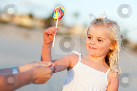 Adorable Little Girl Picking out Lollipop Outside stock photo, Adorable Little Girl Picking out Lollipop from Mom at the Beach. by Andy Dean