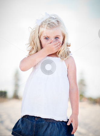 Adorable Blue Eyed Girl Covering Her Mouth stock photo, Adorable Blue Eyed Girl Covering Her Mouth Outside. by Andy Dean