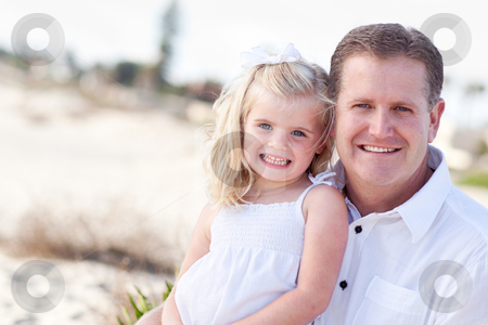 Cute Daughter Cuddles up with Her at the Beach stock photo, Cute Daughter Cuddles up with Her Handsome Dad at the Beach. by Andy Dean