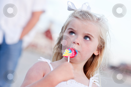 Adorable Little Girl Enjoying Her Lollipop Outside stock photo, Adorable Little Girl Enjoying Her Lollipop Outside at the Beach. by Andy Dean