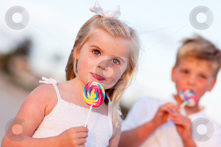 Cute Little Girl and Brother Enjoying Their Lollipops stock photo, Cute Little Girl and Brother Enjoying Their Lollipops at the Beach. by Andy Dean