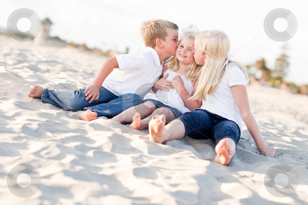 Adorable Sibling Children Kissing the Youngest stock photo, Adorable Sibling Children Kissing the Youngest Girl at the Beach. by Andy Dean