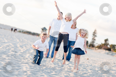 Happy Sibling Children Jumping for Joy stock photo, Happy Sibling Children Jumping for Joy at the Beach as Parents Watch. by Andy Dean
