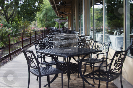 Outdoor Dining Beckons stock photo, Black wrought iron tables and chairs beckon visitors to enjoy outdoor dining on a sunny day by Florence McGinn