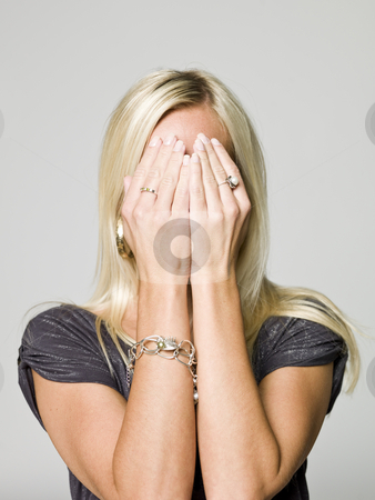 Portrait of a woman hiding in her hands stock photo, Portrait of a woman hiding in her hands by Anne-Louise Quarfoth
