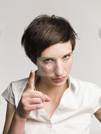 Portrait of a serious woman pointing with her finger stock photo, Portrait of a serious woman pointing with her finger by Anne-Louise Quarfoth