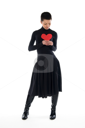 Girl with red heart stock photo, A short hair slim brunette in black dress holds a red paper heart by Nadezhda Shour
