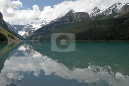 Lake Louise stock photo, Mountains and snowfields reflect in the calm waters of Lake Louise, Alberta, Canada. by Mary Lane