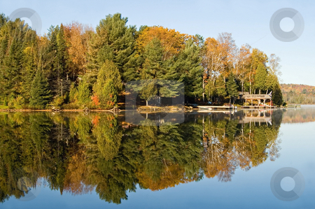Fall Lake stock photo, Boat docks and fall trees, along the shore of a clear blue lake. by Mary Lane