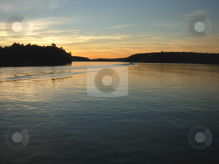 Headed to Shore stock photo, Boat heads for shore at sunset on a lake in cottage country, Muskoka, Ontario, Canada. by Mary Lane