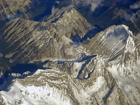 Show in the Rockies stock photo, An interesting day flying over the Rocky Mountains, a little snow, a little cloud, a lot of rock. by Mary Lane