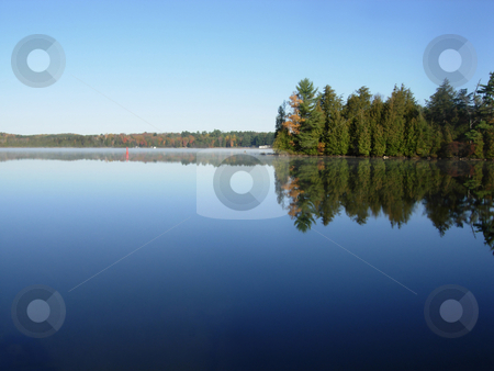 Calm Lake stock photo, Small layer of morning mist along the surface of a calm blue lake. by Mary Lane