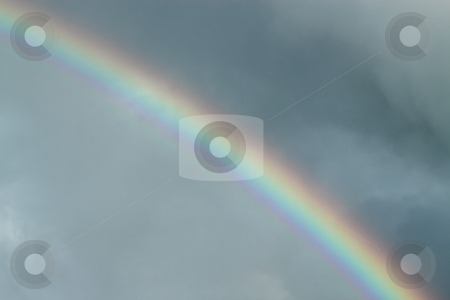 Colorful rainbow in a dark cloudy sky. stock photo, Colorful rainbow in a dark cloudy sky. by Stephen Rees