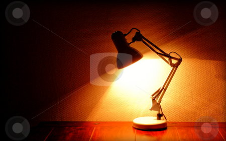 Architect lamp stock photo, Lit architect lamp standing on a table by Kasper Nymann