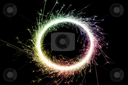 Catherine wheel stock photo, Bright multi colored circle of glowing sparks on a black background by Stephen Gibson