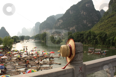 Bamboo rafting on Li-river, Yangshou, China stock photo, Bamboo raft with tourists on the Li-river, the view from the bridge with a straw hat, Yangshou, China by Yulia Zhukova