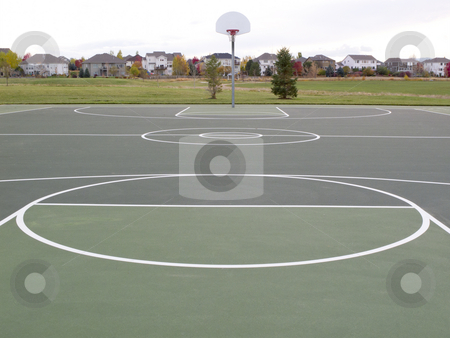 Recreational basketball court stock photo, Green recreational basketball court in a park with houses in background by Marek Uliasz