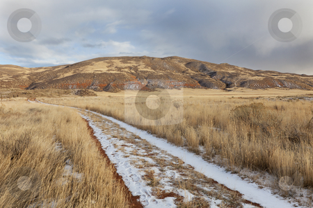 Ranch road in a mountain valley stock photo, Hiking trail on a ranch road with snow and footprints - Red Mountain Open Space in northern Colorado (Larimer County), fall scenery with dry grass by Marek Uliasz