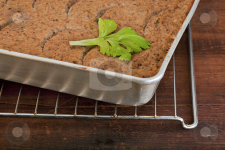 Turkey meatloaf stock photo, Freshly baked turkey meatloaf in a metal tray against old scratched wooden table by Marek Uliasz