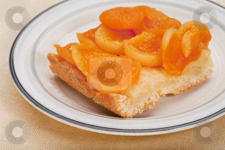 Homemade apricot pie stock photo, A piece of a homemade apricot pie on a round plate against tablecloth by Marek Uliasz