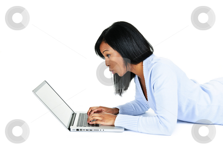 Surprised woman using laptop computer stock photo, Surprised black woman laying with computer isolated on white background by Elena Elisseeva