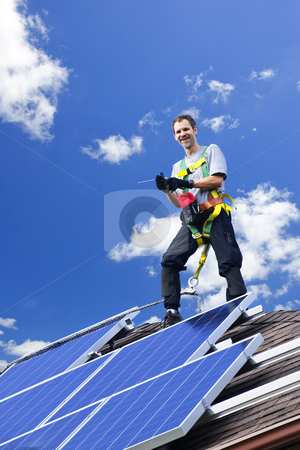 Solar panel installation stock photo, Worker installing alternative energy photovoltaic solar panels on roof by Elena Elisseeva