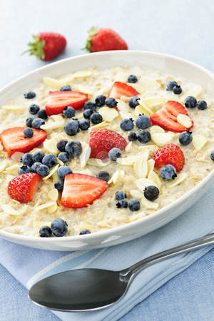 Bowl of oatmeal with berries stock photo, Bowl of hot oatmeal breakfast cereal with fresh berries by Elena Elisseeva