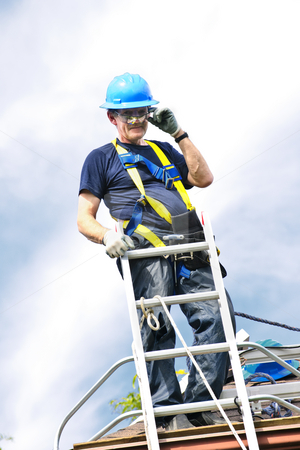 Man working on roof stock photo, Construction worker standing on roof near ladder by Elena Elisseeva