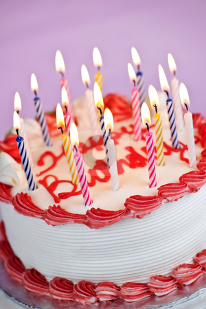 Birthday cake with lit candles stock photo, Birthday cake with burning candles and icing on pink background by Elena Elisseeva