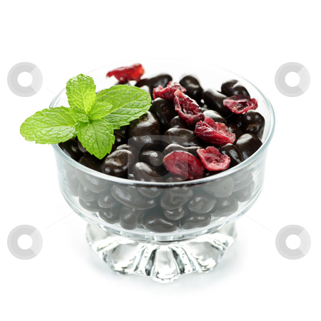 Bowl of chocolate coated cranberries stock photo, Chocolate coated cranberries in glass bowl on white background by Elena Elisseeva