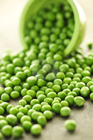 Spilled bowl of green peas stock photo, Closeup on spilling bowl of fresh green green peas by Elena Elisseeva