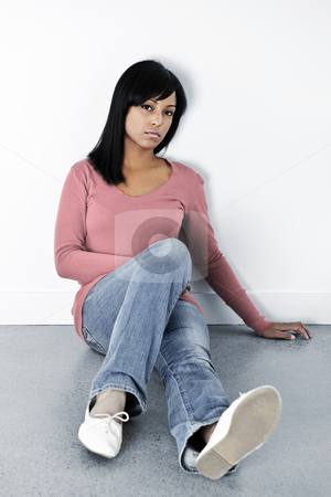 Depressed woman sitting on the floor stock photo, Depressed black woman sitting on the floor against wall by Elena Elisseeva